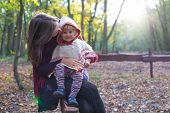 stock photo of kindness  - Smiling little girl on the lap of her kind mother - JPG