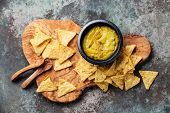 picture of nachos  - Fresh guacamole dip with nachos chips on olive wood background - JPG