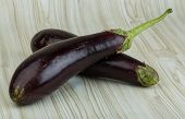pic of aubergines  - Fresh bright raw Aubergines on the wooden background - JPG