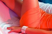 foto of upper thigh  - lower torso of woman laying down wearing short orange satin dress showing arm bracelet and upper thighs shot with red and blue strobes to enhance color - JPG