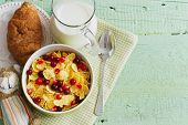 stock photo of croissant  - bowl of cornflakes and berries milk and croissant on a green wooden background - JPG