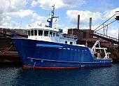 blue white boat in harbor