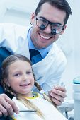 picture of dentist  - Male dentist examining girls teeth in the dentists chair - JPG