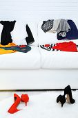 stock photo of shoes colorful  - Colorful clothing on white sofa and female shoes on fluffy carpet and white brick wall background - JPG