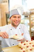stock photo of confectioners  - Handsome confectioner putting cake on the plate - JPG