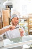 stock photo of confectioners  - Confectioner putting ice cream to the waffle cone in the store - JPG