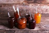 foto of jar jelly  - Jars of tasty jam on wooden background - JPG
