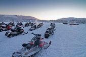 foto of laplander  - Group of snowmobiles ready for a ride in Lapland countryside - JPG