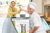 pic of pastry chef  - Confectioner selling ice cream to young woman in the pastry shop - JPG