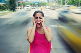 picture of noise pollution  - Portrait of woman standing still in the middle of a street with cars passing by fast screaming stressed and frustrated - JPG