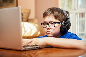 picture of tween  - Tween gamer wearing glasses and headphones playing a videogame on a laptop - JPG