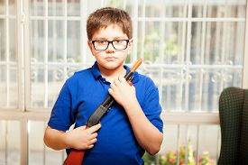 stock photo of tween  - Little nerdy tween holding a toy rifle and acting tough while playing at home - JPG