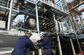 stock photo of refinery  - oil workers with machinery pumps inside large petroleum refinery - JPG