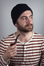 pic of wacky  - Mean bearded sailor grimacing while smoking a pipe - JPG