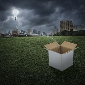 stock photo of thinking outside box  - Glowing light bulb float over box on city background Think outside the box concept - JPG