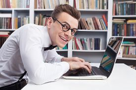 picture of nerds  - Side view of young nerd man in shirt and bow tie typing something on computer and looking at camera with smile - JPG