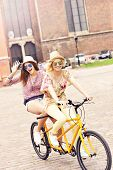 picture of tandem bicycle  - A picture of two girl friends riding a tandem bicycle in the city - JPG