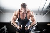 image of pectorals  - Bodybuilder doing butterfly on cable pull for better definition of his arm muscles - JPG