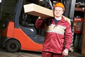 stock photo of forklift driver  - young warehouse worker in uniform in front of forklift stacker loader with box - JPG