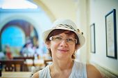 pic of beautiful senior woman  - Beautiful woman in hat sitting in coffee in Rome Italy - JPG