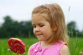 image of lollipops  - cute little girl eating a lollipop on the field  - JPG