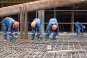 foto of reinforcing  - Worker at construction site is preparing reinforcement cage - JPG