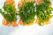 stock photo of rocket salad  - fresh salmon carpaccio sushi sashimi with arugula rocket salad and caper on top - JPG