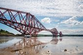 pic of tide  - The famous Forth Cantilever Railway Bridge spans the Firth of Forth on a sunny day reflected in the wet sand at low tide - JPG