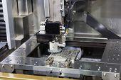 foto of ferrous metal  - wire cut machine cutting high precision mold parts - JPG