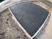 picture of distortion  - The fresh black just laid asphalt at the construction site with wide angle distortion view - JPG