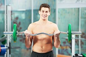 stock photo of triceps brachii  - athlete man workout biceps brachii muscles exercises with training weight in fitness gym - JPG