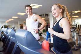 stock photo of vivacious  - Healthy Young Couple Doing Running Exercise on Treadmill Device Inside the Gym with Happy Facial Expressions - JPG