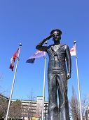 picture of burlington  - A war memorial for the HMCS Burlington from the II world war on the  shore of lake Ontario with flags under blue sky behind.   - JPG