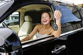 stock photo of luxury cars  - happy woman showing keys of her new expensive status car - JPG
