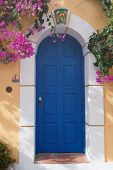 Bougainvillaea at yellow wall and blue door in  Greek Assos