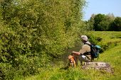 image of bagpack  - Man is resting near the river in nature landscape - JPG