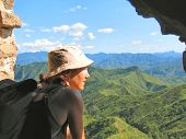 A Trekker Woman With A Hat Looking Over The Mountains And The Jungle From The Great Wall Of China, C