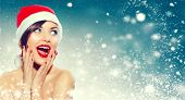 Christmas sale. Beautiful surprised Woman in Santa Claus hat over Xmas Winter Holiday winter backgro poster