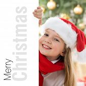 Beautiful young blonde girl in santa hat and red comforter behind white board. Space for text isolat