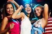 stock photo of night-club  - Group of fashionable girls dancing energetically in night club - JPG