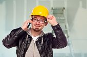 Young Contractor Wearing Hard Hat on Cell Phone In Unfinished House with Drywall and Ladder in the Background.
