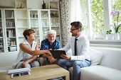 Financial advisor shaking hands with senior woman in living room poster