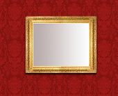 An ornamental gold mirror on a wall of red Baroque wallpaper