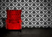 foto of grommets  - A red velvet chair in a dark room with antique wallpaper - JPG