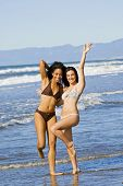 Two happy beautiful diverse friends playing on the beach