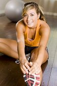 stock photo of ordinary woman  - Young woman exercising at a gym - JPG