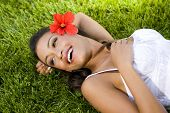 Beautiful exotic woman with a red hibiscus