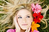 Beautiful woman laying in the grass with flowers in her hair