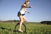young girl monocycling in field
