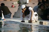 Muslim man performing ablution at Jama Masjid, Delhi, India